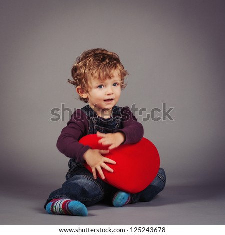 Little kid with red heart. Studio shot. - stock photo