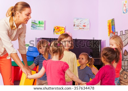 Little kids and teacher roundelay around one girl