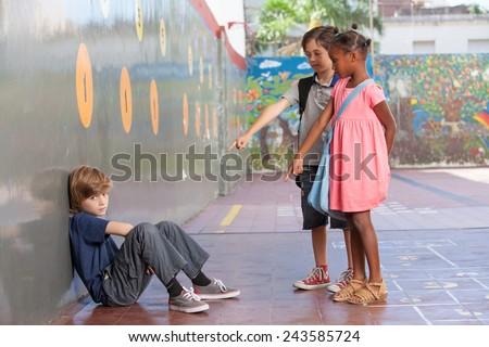 Little kids bullying kid in schoolyard. - stock photo