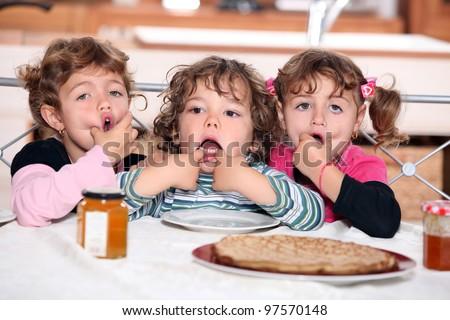 Little kids eating pancakes - stock photo
