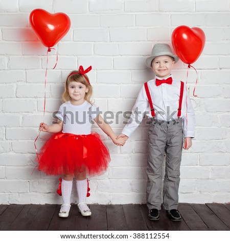 Little kids holding and picking up heart balloons. Valentine's Day and love concept, on white background - stock photo