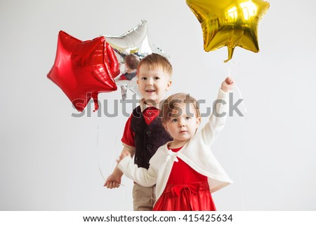 Little kids holding balloons in the form of stars. Children holding a star-shaped balloons. Happy children with colorful shiny foil balloons against a white background - stock photo