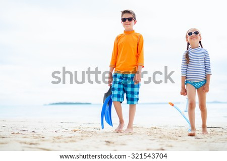 Little kids in rash guards for sun protection with snorkeling equipment on tropical beach during summer vacation - stock photo