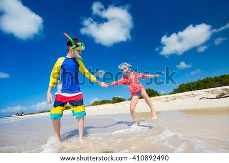 Little kids in rash guards for sun protection with snorkeling equipment on tropical beach having fun during summer vacation - stock photo