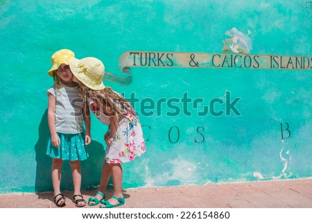 Little kids near big map of Caribbean island Turks and Caicos painted on the wall - stock photo