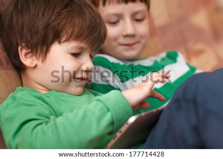 Little kids playing on tablet, wireless technology in family - stock photo