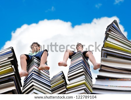Little kids sitting on large stack of books - stock photo