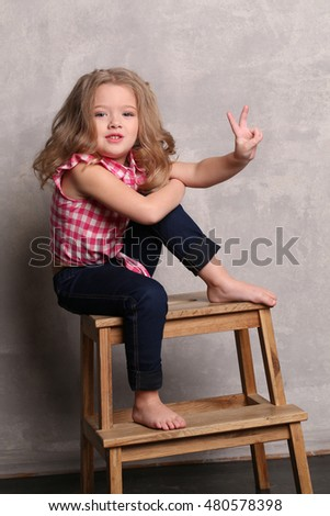Little lady in plaid shirt posing on a chair. Gray background