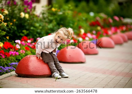 little laughing blond girl in brown skirt and pink cardigan is playing on the road in the garden with red flowers - stock photo
