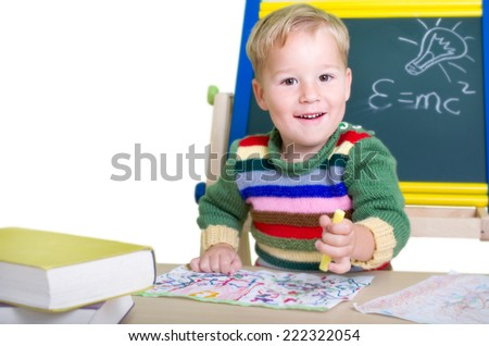 Little laughing boy playing school with a blackboard