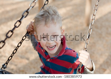 little laughing boy swinging at the playground