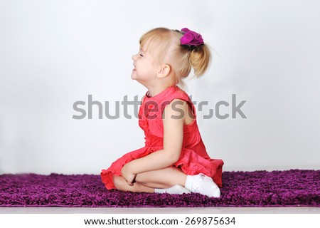 Little laughing girl is sitting on a purple carpet in the studio. - stock photo