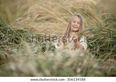 little laughing pretty girl with long blond hair sitting in the field of wheat of corn at summer - stock photo