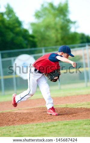 Little league baseball boy pitching during a game. - stock photo