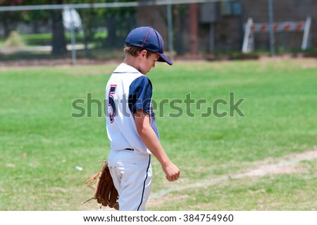 Little league baseball player looking down at the field wearing white uniform. - stock photo