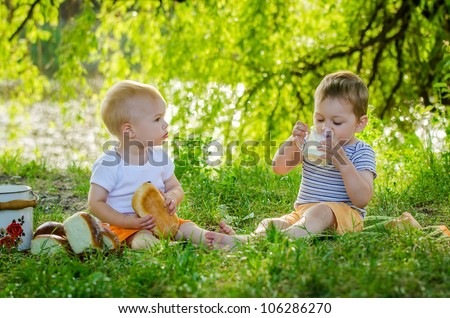 Little lovely boys drinking milk on picnic
