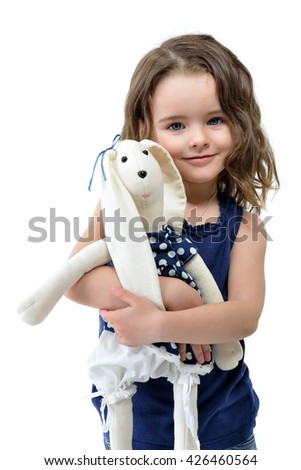 Little lovely girl embracing her loved hand made toy, studio shot over white background.