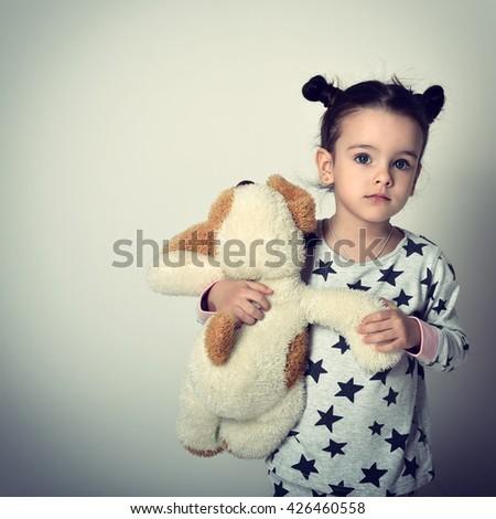 Little lovely sleepless girl in pajamas holding her loved plush toy. Insomnia. Children's fears. - stock photo
