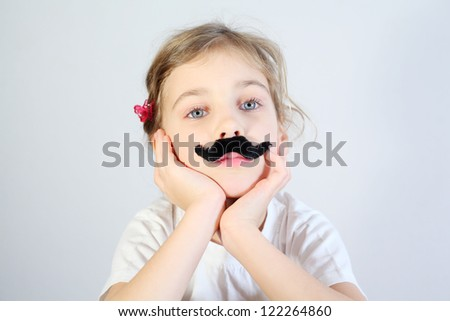Little melancholy girl in white with glued fake black mustache. - stock photo