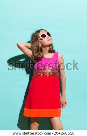 Little miss sunshine. Young fashionable girl in sunglasses posing in sunlight. Three quarter length studio shot on teal background.