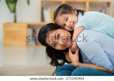 Little mixed-race girl hugging her beautiful mother - stock photo