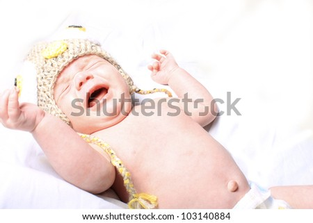 Little month old baby crying wearing hat and showing belly button on a white background - stock photo