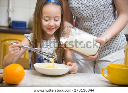little  mothers helper. Small girl going to beat the dough for pancakes. Mom teach daughter to cook - stock photo
