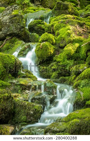 Little mountain stream over mossy rocks - stock photo