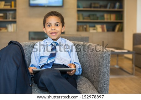 Little mulatto boy in a business suit with the tablet sitting in a chair in a business center