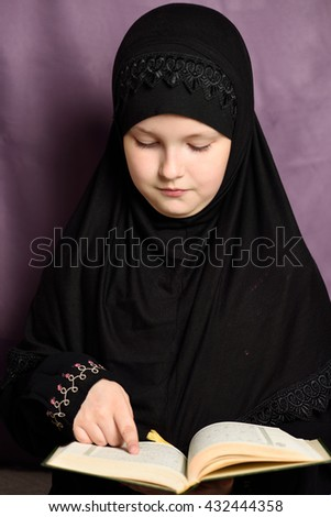 Little Muslim girl with the holy Quran - stock photo