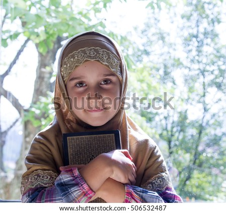 Little Muslim girl with the holy Quran.