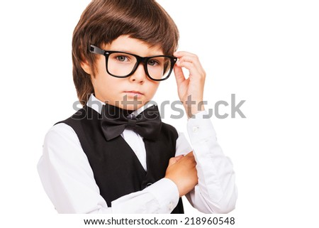 Little Nerd. Cute little boy adjusting his glasses and looking at camera while standing isolated on white - stock photo