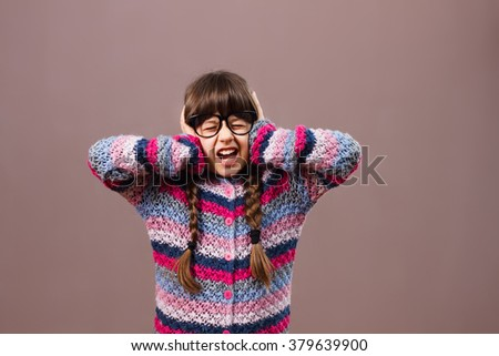 Little nerdy girl is frustrated because of something and  she can't  listen no one anymore.Frustrated little nerdy girl - stock photo