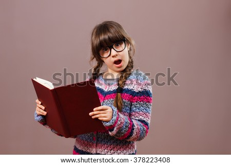 Little nerdy girl is surprised by something she has seen in her book.Surprised little nerdy girl with book - stock photo
