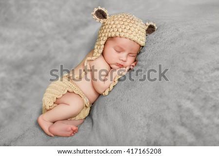 Little newborn baby boy 7 days, sleeps. newborn baby curled up sleeping on a blanket. Eight day old smiling newborn baby boy. - stock photo