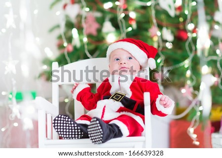 Little newborn baby boy in Santa outfit sitting under a Christmas tree in a white chair - stock photo