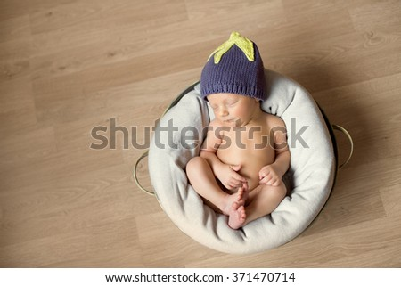 little newborn baby boy or girl in violet hat with close eyes sleeping sweetly in the white basket