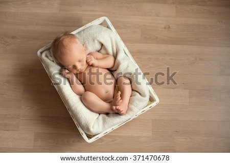 little newborn baby boy or girl with close eyes sleeping sweetly in the white basket