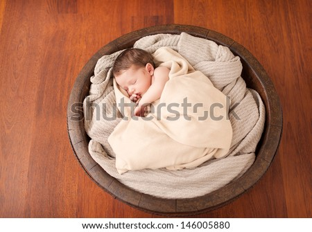 Little newborn baby in a wooden bowl - stock photo
