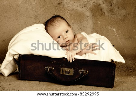 Little newborn baby of 18 days old in an old vintage leather suitcase