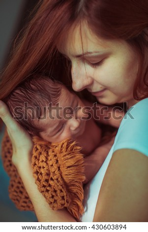 little newborn baby sleeps in the arms of mother - stock photo
