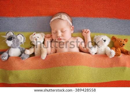 Little newborn girl 11 days, sleeps. Beautiful newborn girl wihh bear toy - stock photo