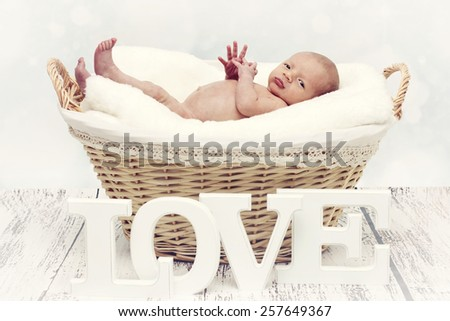 Little newborn lying in the wicker basket and looking to the camera