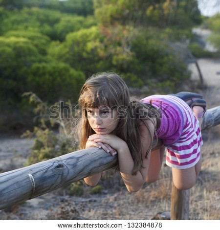 Little nine-year girl climb on vintage rural fence. - stock photo