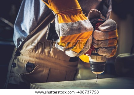 Little of Residential Construction Works. Men Fixing Wooden Shelf with His Driller. - stock photo