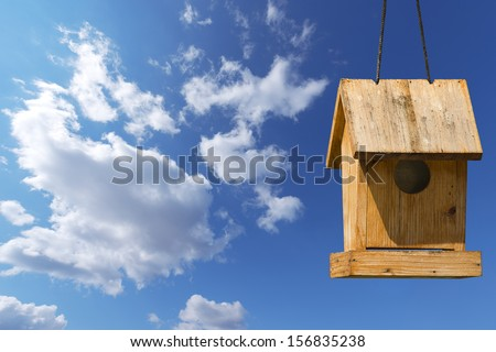 Little Old Birdhouse on Blue Sky / Old wooden birdhouse on a blue sky with free space for text - stock photo