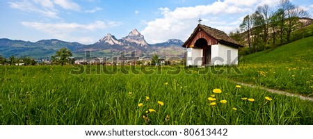 Little old chapel in a blooming green field - stock photo