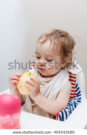 Little one year old girl eating big apple while sitting in highchair in dining room. Baby looking straight to the camera. Selective focus on child head. - stock photo