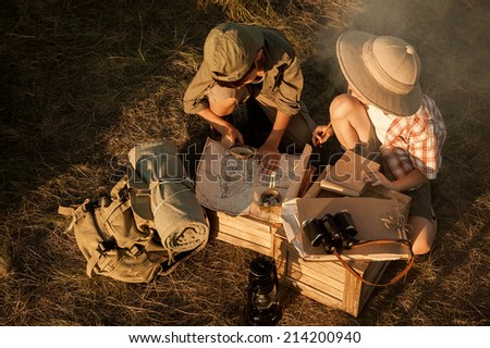 Little ones - boy and girl - studying the map of the area and the upcoming campaign at sunset  - stock photo