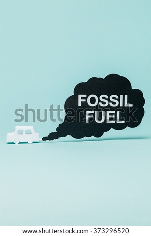 Little paper car creating carbon dioxide emissions while running. - stock photo